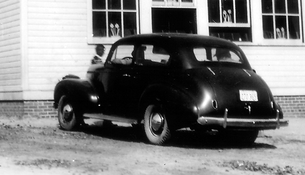 Black and white photograph of Principal Archer's Buick automobile parked in front of the Vienna Colored School.